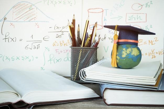 Chapeau de graduation sur les crayons avec le graphique d'équation arithmétique de formule