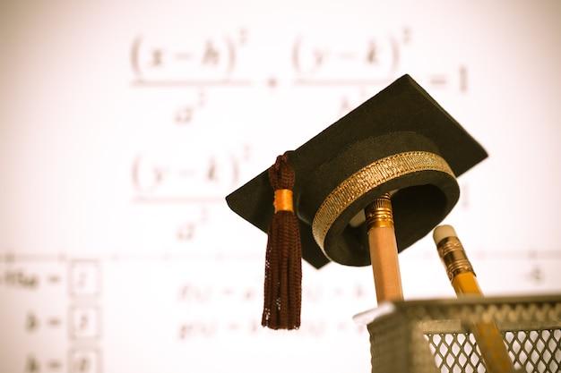 Chapeau de graduation sur les crayons avec un graphique d'équation de formule sur l'écran du projecteur à l'université