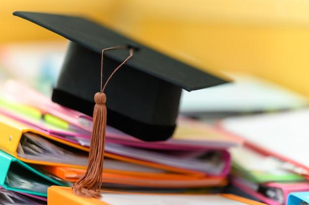 Chapeau de graduation noir placé sur un dossier sur un bureau
