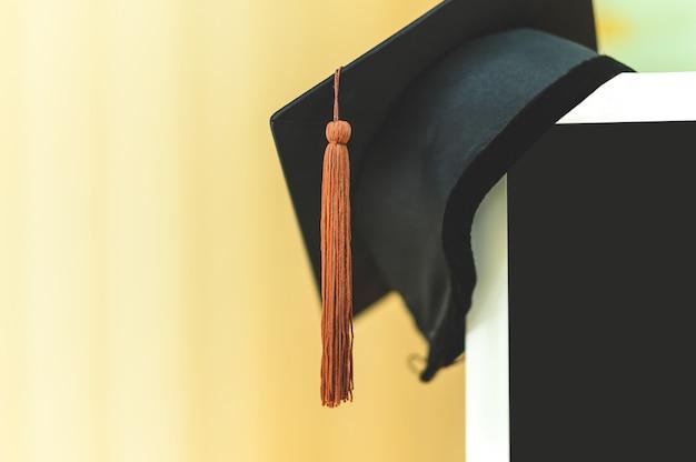 Chapeau de graduation noir placé sur un écran d'ordinateur