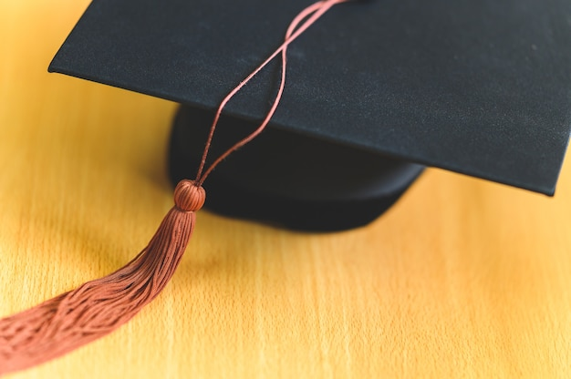 Chapeau de graduation noir placé sur une table en bois