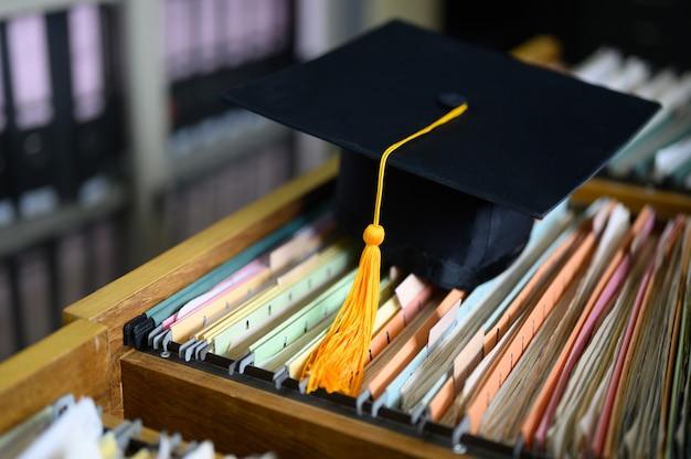 Chapeau de graduation noir et pompon jaune posés sur le meuble