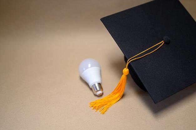 Chapeau de graduation noir posé sur du papier brun