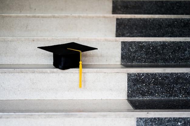 Chapeau de graduation noir posé sur les marches du couloir