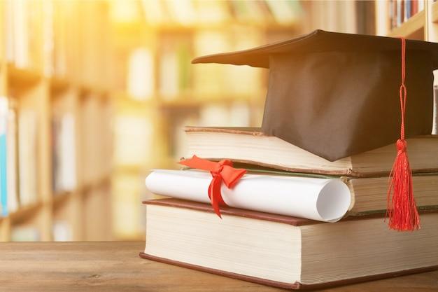 Chapeau de graduation sur pile de livres et diplôme