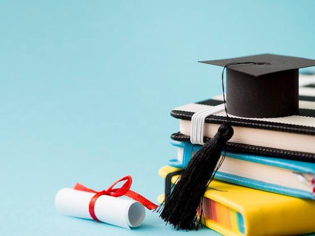 Chapeau de graduation sur une pile de livres avec espace copie