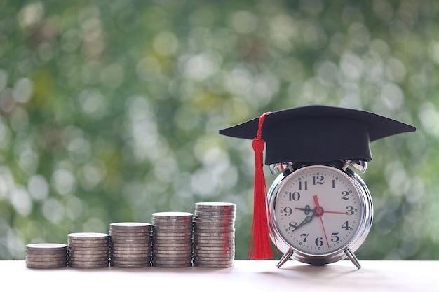 Chapeau de graduation sur réveil avec pile de pièces d'argent sur fond vert naturel, économiser de l'argent pour le concept d'éducation