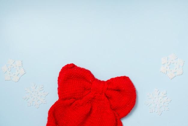 Chapeau d'hiver en tissu rouge avec décor de flocons de neige sur bleu