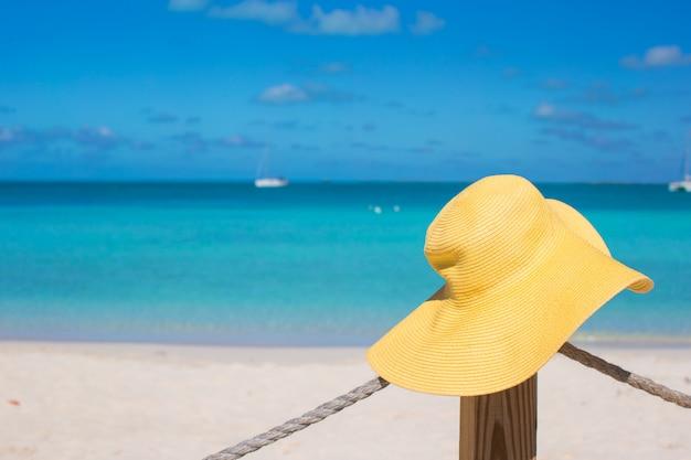 Chapeau jaune sur la barrière de plage à l'île des caraïbes