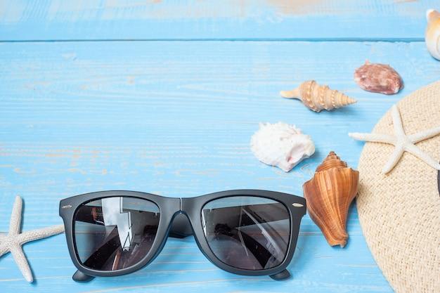 Chapeau, lunettes de soleil et coquille sur bleu
