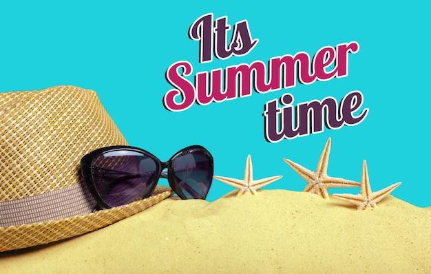 Chapeau, lunettes de soleil et étoile de mer sur le sable son heure d'été