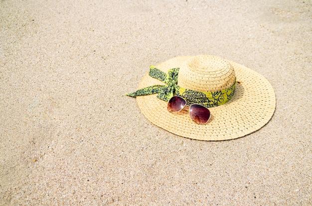 Chapeau et lunettes de soleil sur le sable de la plage