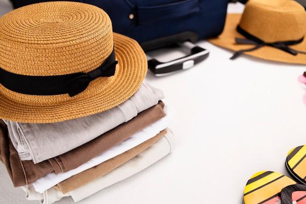 Chapeau lunettes de soleil tongs et accessoires de plage bagages articles de voyage valise et chapeau se préparant pour les vacances ou l'espace de copie de voyage