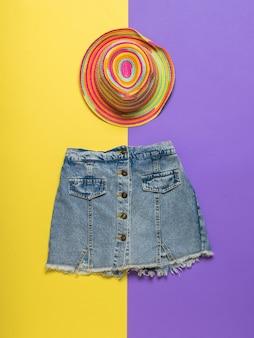 Chapeau multicolore et jupe en jean sur une surface jaune et violette
