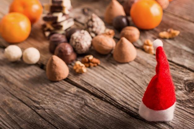 Chapeau de noël avec du chocolat et orange sur la vieille table en bois