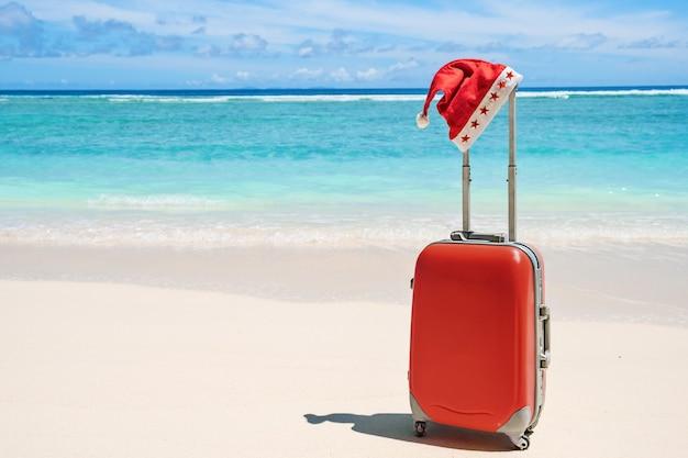 Chapeau de noël du père noël rouge sur la poignée de bagages de voyage rouge