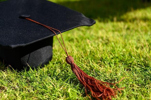 Le chapeau noir et le certificat des diplômés universitaires sont placés sur des feuilles vertes.