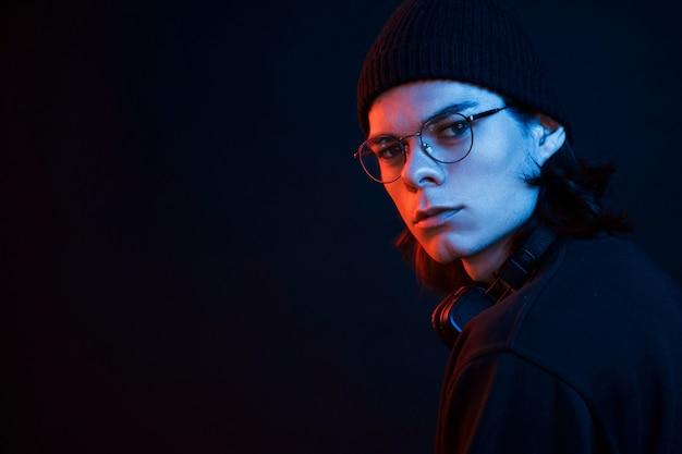 En chapeau noir. studio tourné en studio sombre avec néon. portrait d'homme sérieux