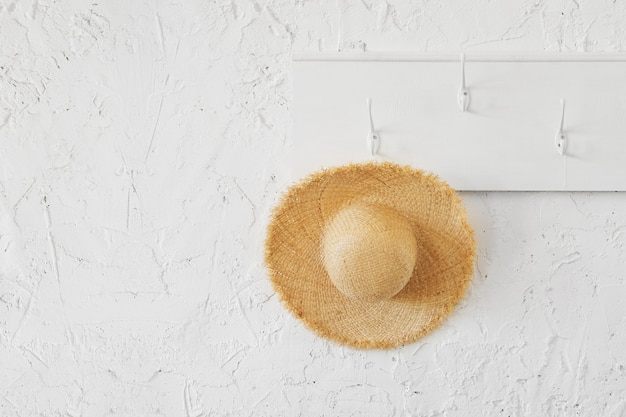 Chapeau en osier tropical sur un cintre en bois blanc dans un intérieur minimaliste.