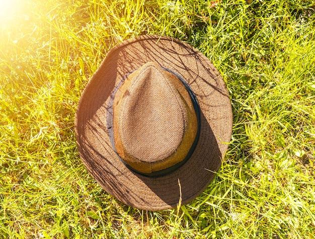 Chapeau de paille allongé sur l'herbe ou la pelouse en été.