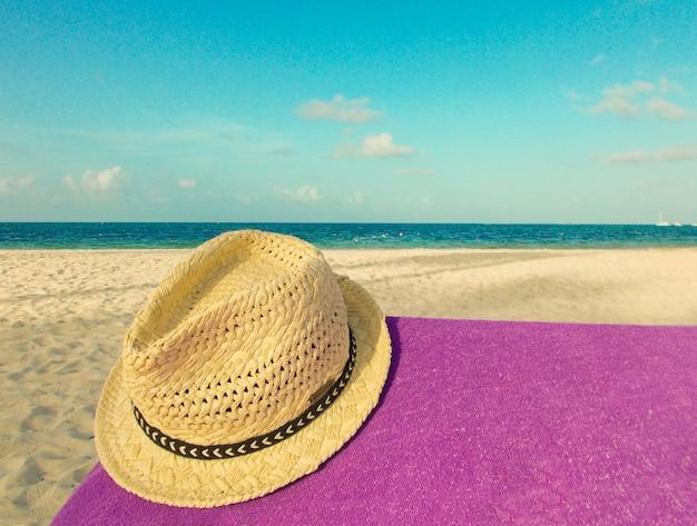 Chapeau de paille allongé sur une serviette violette sur la plage