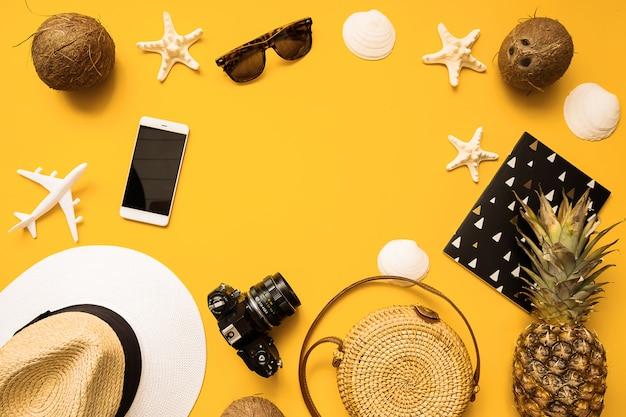 Chapeau de paille, appareil photo argentique rétro, sac en bambou, lunettes de soleil, noix de coco, ananas, coquillages et étoile de mer, avion, carnet et téléphone