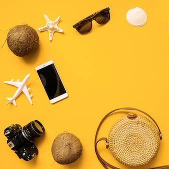 Chapeau de paille, appareil photo argentique rétro, sac en bambou, lunettes de soleil, noix de coco, ananas, coquillages et étoile de mer, avion
