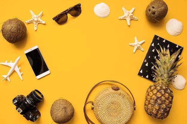 Chapeau de paille, appareil photo argentique rétro, sac en bambou, lunettes de soleil, noix de coco, ananas, coquillages et fond d'étoiles de mer