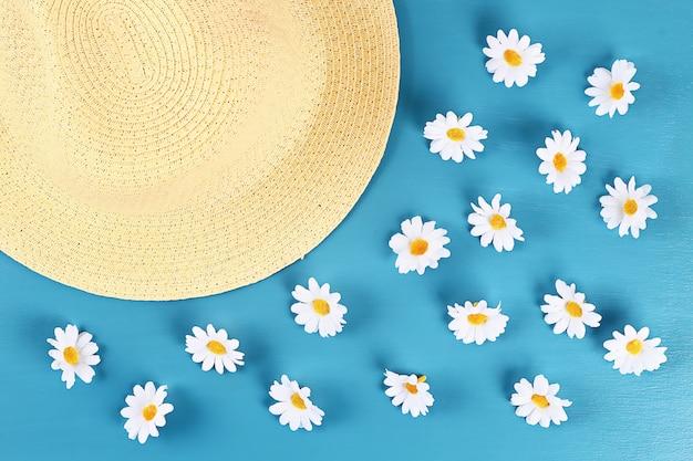 Chapeau de paille à la camomille sur fond bleu. vue de dessus. fond d'été. lay plat.