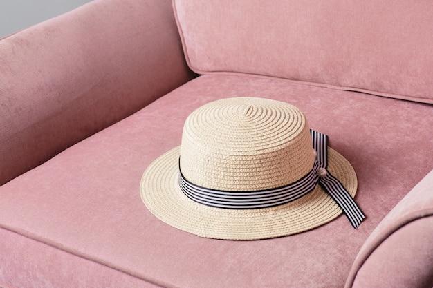 Chapeau de paille sur chaise rose