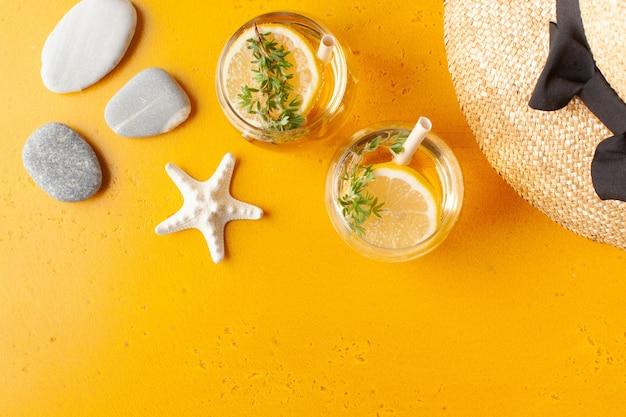Chapeau de paille d'été étoile de mer rafraîchissante limonade et rochers sur l'espace de copie jaune