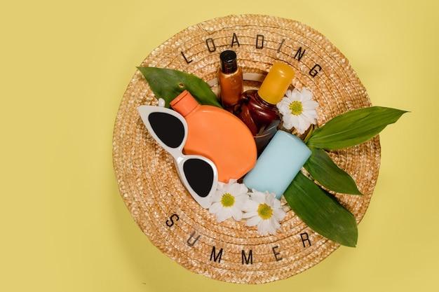 Chapeau de paille d'été pour femmes sur fond jaune, vue de dessus, espace de copie à plat. concept de vacances de voyage d'été, élément unique. texte summer à partir de lettres et de fleurs de camomille sur fond jaune.