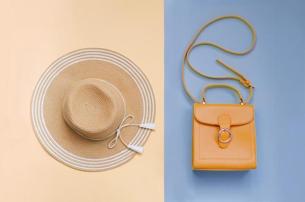 Chapeau de paille d'été et sac orange sur bleu et rose