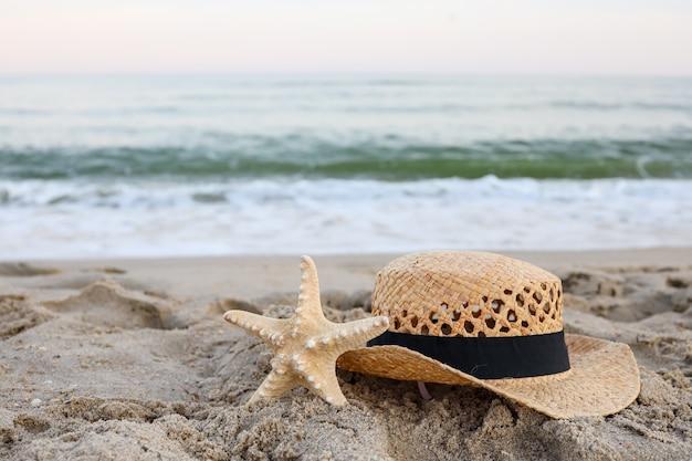Chapeau de paille et étoile de mer sur le beau sable au bord de la mer