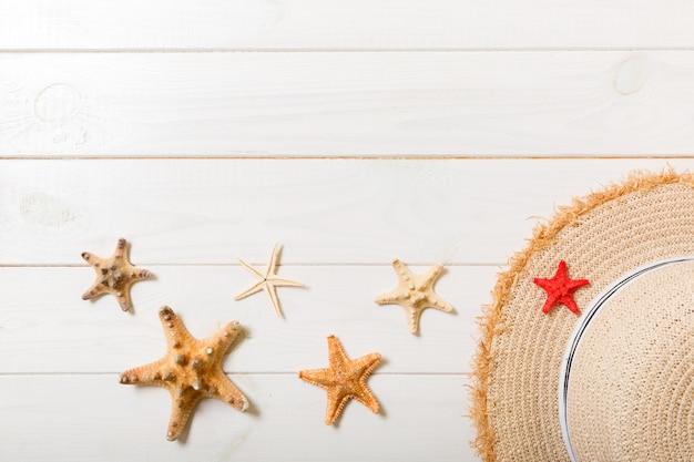 Chapeau de paille et étoile de mer sur un fond en bois blanc. concept de vacances d'été vue de dessus avec espace de copie.