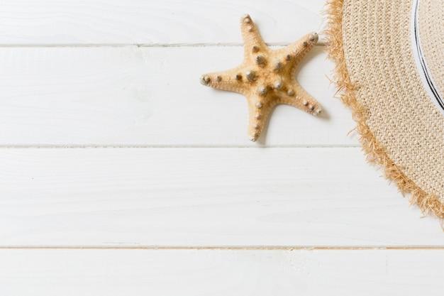 Chapeau de paille et étoile de mer sur un fond en bois blanc. vue de dessus concept de vacances d'été avec espace copie