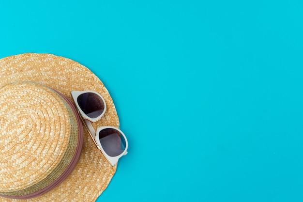 Chapeau de paille femme et lunettes de soleil pour les vacances à la plage vue de dessus