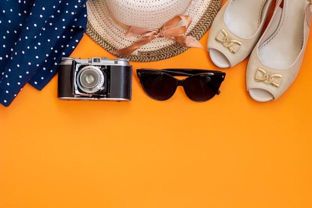 Chapeau de paille femme avec des lunettes de soleil ruban noir jupe à pois bleus sandales appareil photo rétro vintage isolées sur un mur orange de couleur vive
