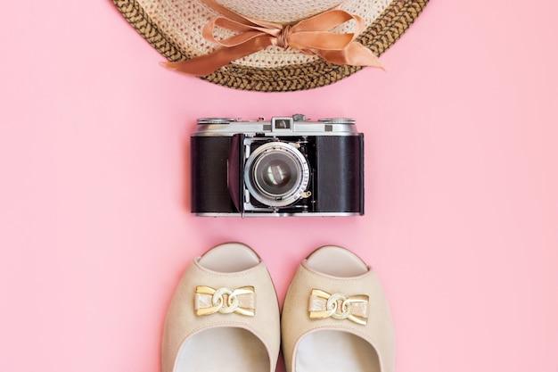 Chapeau de paille femme avec ruban vieilles sandales appareil photo rétro vintage isolés sur un mur rose de couleur claire