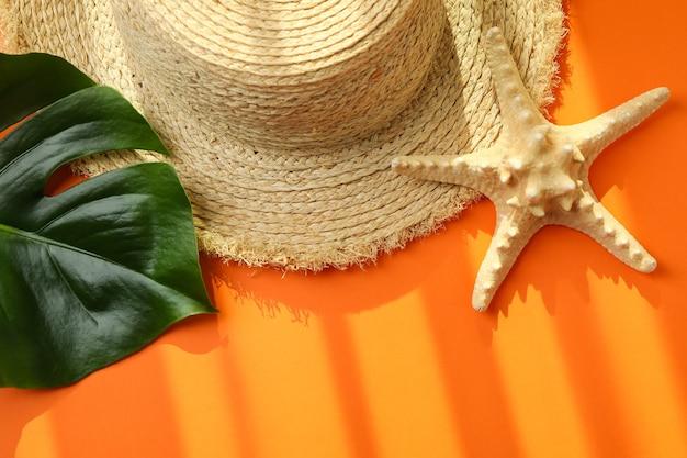 Chapeau de paille, feuille de palmier et étoile de mer sur orange