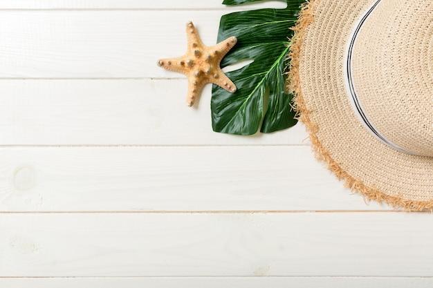 Chapeau de paille, feuille verte et étoile de mer sur un fond en bois blanc. concept de vacances d'été vue de dessus avec espace de copie.