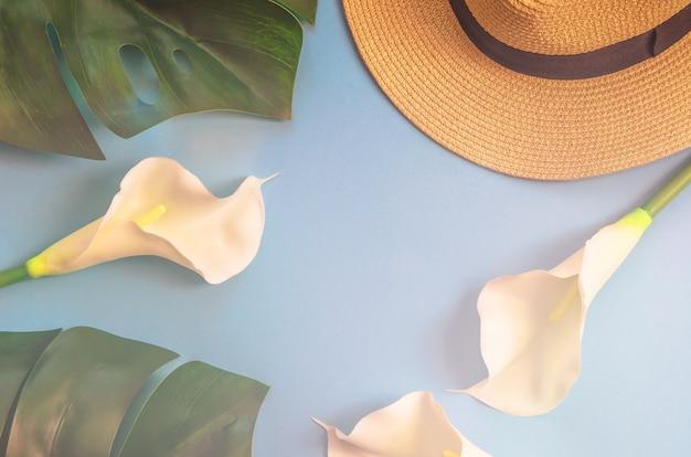 Chapeau de paille avec des feuilles tropicales monstera et callas blancs, sur fond bleu clair.
