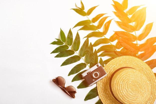 Chapeau de paille avec des feuilles vertes et vieil appareil photo sur fond blanc été fond vue de dessus sun flare