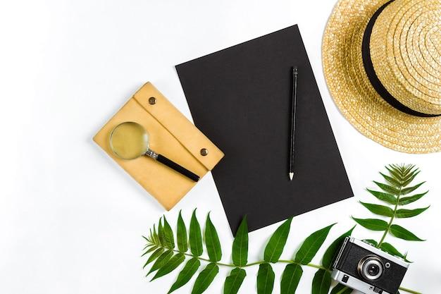 Chapeau de paille avec des feuilles vertes et vieil appareil photo sur fond blanc vue de dessus de fond d'été