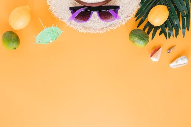 Chapeau de paille avec des lunettes de soleil, des coquillages et des fruits