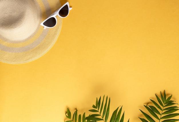 Chapeau de paille et lunettes de soleil sur fond jaune avec des feuilles de palmier fond horizontal de vacances d'été, espace copie