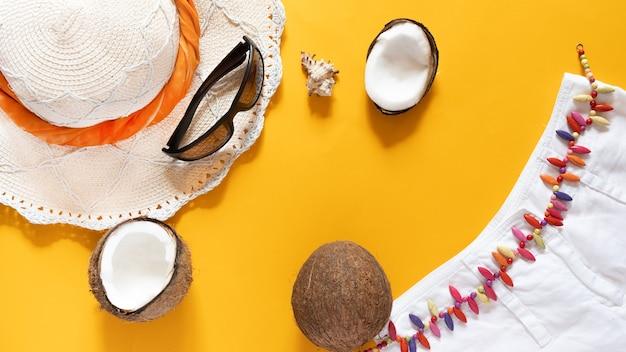 Chapeau de paille, lunettes de soleil, moitiés de noix de coco, coquillage et short blanc sur fond jaune