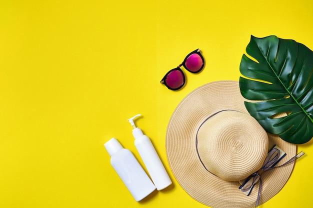 Chapeau de paille, lunettes de soleil roses et feuille de palmier sur fond jaune. concept minimal créatif. vue de dessus mise à plat