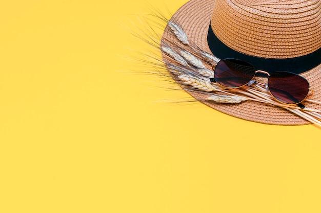 Chapeau de paille marron avec des lunettes de soleil et des épis de blé secs sur jaune