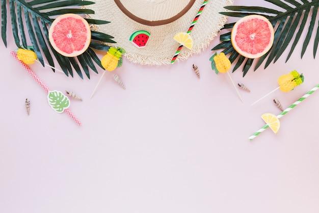 Chapeau de paille avec des pamplemousses et des feuilles de palmier